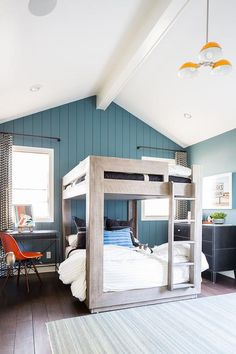 An orange light hangs from a vaulted ceiling over a gray rug placed in boys' shared bedroom in front of an RH Baby & Child Thayer Bunk Bed.