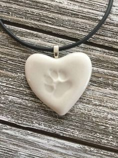 An elegant way to display your love and affection for your beloved pet who has crossed over the rainbow bridge. Made from English porcelain, simply stamped with a paw print and glazed with a clear shiny glaze. Measures almost 1.5 across and comes with an attached silver toned bale and
