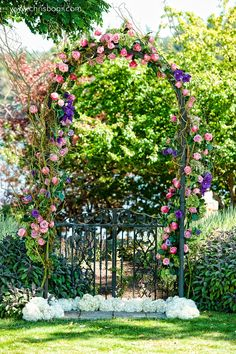 Took an arch from drab to fab with some curly willow, bright roses, and hydrangea.