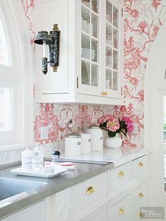 White countertops and kitchen cabinetry can quickly overwhelm a room and make it feel cold. Warm it up in a jiffy with a high-contrast wallpaper pattern that surrounds the cabinets with inviting color.
