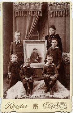 A mother and her five sons gather around a photograph of her husband and their father.