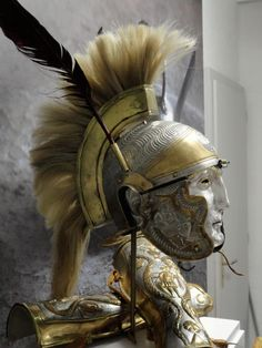 """Roman parade helmet with horsehair plume and goose feathers, silvered, with brass applique, and matching greaves. """