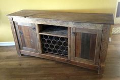 """This rustic sideboard was built with our reclaimed barn oak. The wine rack in the center was built with some reclaimed split ring washers salvaged from some of our beams. The plank used for the top is a very unusually wide piece measuring about 20"""" wide. Product Used: Sanded Barn Oak Plank  Credit: Matt Schmid Construction"""