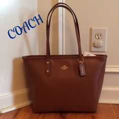 "NWT  COACH LEATHER CITY ZIP TOTE SHOULDER BAG Simply Beautiful!!!  Carry year round with this beautiful color of Saddle. Coach logo on front and hang tag. This is a crossgrain leather tote shoulder bag with a zip closure. Dual shoulder straps w/9.5"" drop. Gold hardware. Interior features black sateen fabric w/large zip pocket and 2 slip pockets. Measures 12""x11""x5"". Coach Bags Totes"