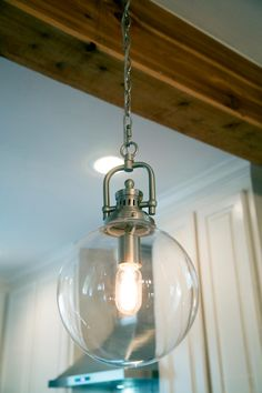 The stylized globe fixtures with incandescent bulbs provide soft illumination above the breakfast bar.