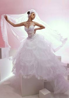 This wedding dress looks modern and fashionable with spaghetti sweetheart neckline. The bodice is embellished with lace and tulle pieces. The soft tulle skirt is multi-tiered with pleated hemline.