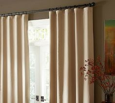 Drop cloth curtains.  Cheap. Nice texture.  I like the dark metal of the rods she chose too.
