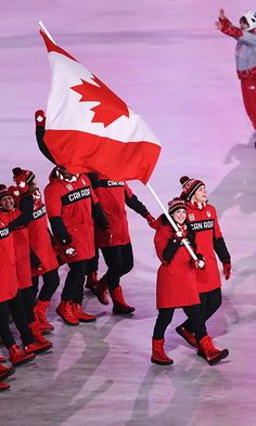 Ice dance partners Tessa Virtue and Scott Moir lead the crowd of Canadian flag bearers. Photo: © Getty Images