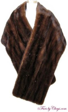 SOLD! Long Mahogany Mink Stole #MM731; Excellent Condition; One Size Fits Most. This is an elegant genuine natural very dark mahogany mink fur stole in a long length for a dramatic look. It has a Lewitz Furs label and the lining is a dark taupe patterned lining with metallic gold thread accents -- stunning! It is an open design (no closures). This luxurious mahogany mink stole will transform an ordinary evening into something magical!