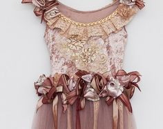 This beautiful dress has been handmade using quality fabrics.  A selection of velvet and tulle with handmade ribbon roses embellished with diamantes and crystals. Such a pretty soft apricot, this dress would make a lovely pageant dress, party dress or flower girl dress.  Size 3-4 and is the only one in stock.  I can make other sizes to order. Please note, each dress is handmade and may have minor differences.