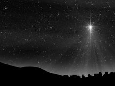 Surrounded by hundreds and hundreds of twinkling stars in a beautiful night sky, a large Christmas Nativity star shines down upon the silhouetted  town of Bethlehem with white rays of light and sparkling particles.