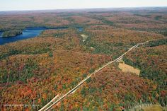 """Highway 60 in Algonquin Park on September 25, 2013. Peck Lake Trail Parking Lot is in the foreground, Source Lake in the background. Found Lake is far right along with the wetland known as """"Toad Gulch"""" (between Peck Lake Trail and Found Lake).  Fall aerial images of Algonquin Park's fall colour. www.algonquinpark.on.ca"""