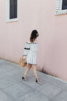 Off-the-shoulder neutral dress with pom pom fringe, a chic black hat, + strappy heels via For All Things Lovely | Tularosa dress, Valentino heels, Cult Gaia handbag, Janessa Leone hat, and Celine sunnies
