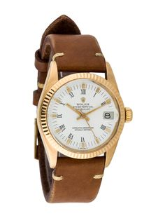 Ladies' 18K yellow gold 31mm Rolex Oyster Perpetual Datejust Watch with acrylic crystal, fluted bezel, white flat dial, Roman numeral and luminous stick hour markers, luminous baton hands, stick sweeping seconds hand, cyclops date display at 3 o'clock position, signed fluted screw down crown, brown leather strap and tang buckle closure.  Note: This watch has been evaluated by our Watch Specialist and Horologist.   Watch Condition: Grade 1 Collection: Oyster Perpetual Model Name: Datejust…