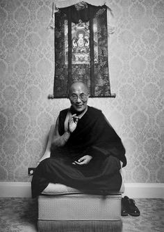 His Holiness the Dalai Lama with a thangka painting in a black and white photo.