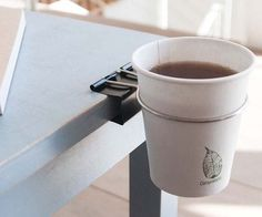 Clip your cups on table tops or shelves. With the Cup Clip Multifunctional Clip, you can not only clip your cup on the side of a table or shelf but also use it as a hook for hanging small objects.