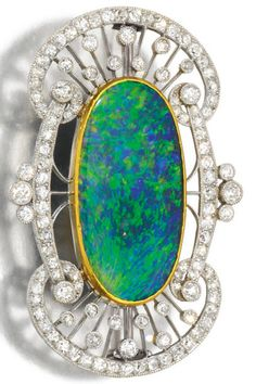 An Edwardian opal and diamond brooch, circa 1910. Set with a polished opal within an openwork frame millegrain-set with circular- and single-cut diamonds. #Edwardian #brooch