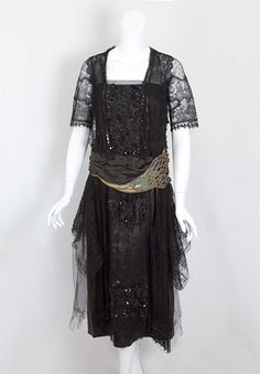 Beaded black lace dress, c.1918 $1400.The dress is constructed with layers of lace and tulle over a black satin lining; and it closes on the side front with small snaps and hooks. The bodice and skirt front are embellished with jet-black beads and sequins, adding sparkle to the black-on-black design.  Masterfully applying the principle of contrast, the designer uses color only on the black satin cummerbund, which is embroidered with three shades of blue silk floss and gold tone beads.