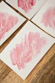 La caligrafía se une a las acuarelas en estas tarjetas para mesas que siguen el diseño de las invitaciones de boda. El objetivo es un look moderno y romántico