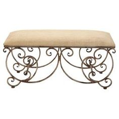 """Cushioned bench with a scrollwork metal base and upholstered cream seat.  Product: BenchConstruction Material: Metal, foam and fabric  Color: Cream and bronze     Dimensions: 18"""" H x 40"""" W"""