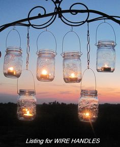 "Anyone can makes these out of Canning Jars and old wire coathangers.  OR you can buy them at Pottery Barn.  I like to make these and hang them from trees when entertaining outside.  I put a little sand or pebbles in the bottom of each jar to hold the candle in place.  You can also use colored glass marbles or sand with glitter added for a more ""sparkly"" outdoor party :)"