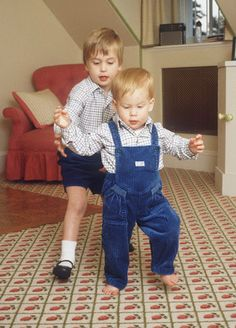 Prince William giving his little brother Prince Harry some tips on walking. Taken in the nursery at Kensington.