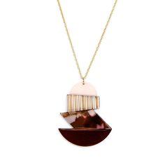 Raspberry is a geometric pendant constructed from striped and coloured acetate pieces, mounted on a golden brass chain.Total length: 58 cm.<i>Raspberry es una figura geométrica construida con piezas de acetato de diferentes estampados y colores que cuelga de una cadena de latón.Largo collar: 58 cm.</i>
