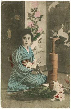Old Japan: Attractive, tinted vintage postcard of a pretty Japanese girl, kneeling in front of a stand made of bamboo, arranging flowers for