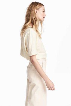 Cremefarben. Kurzarmshirt aus etwas festerem Baumwolljersey mit Zier- und Steppnähten. Modell mit geradem Schnitt und abgerundeten Schultern.