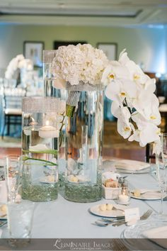 Three-vase centerpieces with floating candles, white cascading orchids and jeweled detail