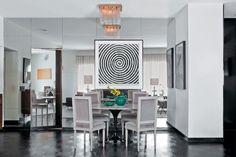 """Integrado à sala de estar, o ambiente de jantar foi instalado próximo à parede que separa a área social da cozinha do apartamento. """"Para ocultar essa divisória e conferir um acabamento nobre ao espaço, revesti a parede com placas de espelho"""", explica o designer de interiores Beto Galvez, autor do projeto. A proposta amplia a luminosidade natural da área ao refletir a janela. Atenção ao detalhe: a porta pivotante também foi espelhada, preservando a unidade visual do painel."""