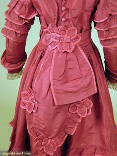 "1870 - Girl's Silk Dress and High Boots. Deep dusty rose faille 1-piece day dress, self fabric flounce trim, separate belt w/ attached peplum, buckram lining, Ch 31"", W 23.5"", L 43"", excellent, matching high button boots, low Louis heel & red speckled white china buttons, stamped on sole "" H. Wireman Philada."", 2"" x 8.25"", heel 1.25"", (shoes worn at edges) fair."