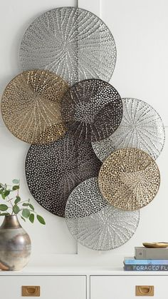 A stunning work that seems to float airily across your wall the Adele Metal Wall Art is formed of laser-cut metal disks welded together forming a striking display. Each disk has a lacy delicately textured cut-out design inspired by natural elements.