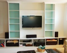 """Very creative way to not only add """"built in"""" bookcases, but a nice way to hang the flat screen."""