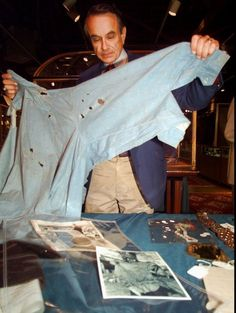 Greg Martin, director of the Arms and Armor department at Butterfield Action house. Holds up the bullet ~ riddled death shirt of Clyde Burrow. It was auctioned for $$ 75,000 in San Francisco 1997