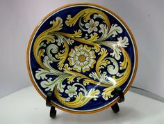 Piatto in ceramica artistica di Caltagirone. di ArtCeramicJewelry  Dish ornamental molded on the lathe and hand-decorated with floral patterns on a cobalt blue background, traditional decor. It can be hung on the wall by a hook inserted into the hole in the back of the dish or it can be supported on a support to embellish your home with a unique piece. The wrought iron support is free.  #etsy #handmade #ceramics #pottery #Caltagirone #sicily #art