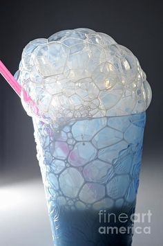 Blowing milk bubbles out of a glass with straw