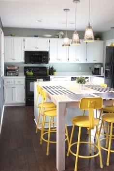 Bright yellow bar stools in a kitchen with small touches of green + a whole bunch of other colored stool options