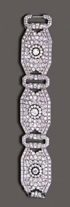 AN ART DECO DIAMOND BRACELET  Designed as three articulated and pierced old European-cut diamond plaques, of octagonal outline and floral motif, each centering upon an independent old European-cut diamond, joined by similarly-set oblong links, mounted in platinum, circa 1935, 7½ ins.