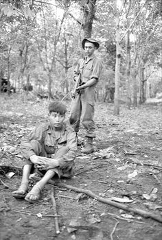 Private David Collins, 6RAR, Australians, guards a captured Viet Cong soldier found hiding on the battlefield the next day