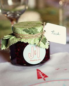 Jessie and Tyler picked raspberries the summer before the wedding, and Jessie and her mother made jam. The jars were covered with smaller pieces of the same fabric found on the reception's tabletops and were finished with twine. The custom stickers and handwritten labels double as place cards.