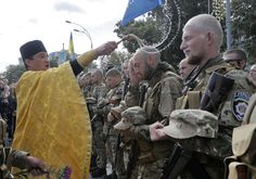 A priest blesses volunteers before they were sent to the eastern part of Ukraine to fight against pro-Russian separatists, in Kiev, Ukraine, on August 26, 2014. (AP Photo/Efrem Lukatsky)