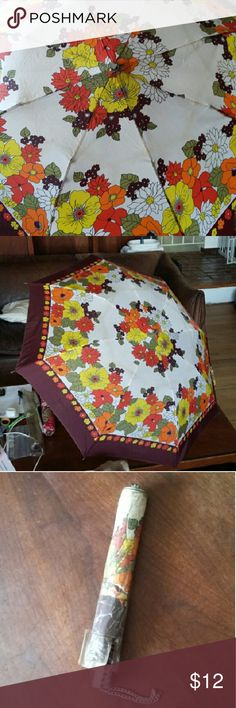 Vintage floral umbrella Stay dry in style under this funky 70s flower print umbrella with chain strap and plastic sleeve. Wear consistent with age, including a chunk out of the button on top (see photo.) Accessories Umbrellas