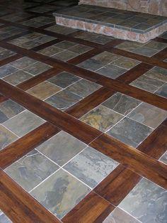 Image from http://affordableflooringconnection.com/Images/custom_wood_tile_inlaid_floor/slate_floor_hardwood_inlay_slate_hearth.jpg.