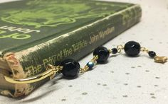 Black and gold beaded bookmark Beaded Bookmarks, Organza Gift Bags, Heart Of Gold, Black Glass, Gold Beads, Floral Motif, Heart Charm, Metal, Gifts
