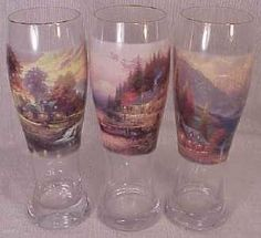 "Set of 3 Thomas Kinkade Pilsner Glasses #1 by Bradford Exchange. $19.99. hand, hard fired. Thomas Kinkade imagery. Crystal pilsner glasses. 22 carat gold rim. This is a beautiful set of three Thomas Kinkade Crystal Pilsner Glasses featuring three different ""Mountain Hideaway"" scenes. This is the first of four sets that make up a twelve glass collection. Each heirloom quality crystal glass is hand fired and finished with a glistening 22 carat gold rim and limited to 95 firing day..."
