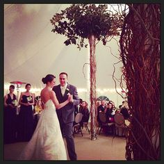 Use the poles of the tent to make magnolia trees! Great idea for wedding decor