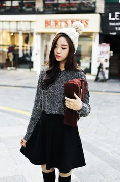 Grey textured sweater, black skirt, white beanie