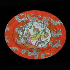 """English Chinoiserie Platter Antique Orange. Extraordinary and hard to find large antique English Chinoiserie bright orange oval platter decorated with foo dogs / lions and a center white reserve with a group of five people, in an outdoor setting, playing a board game. The platter is marked on the underside with an impressed ASHWORTH in capital letters and a hand-painted red code B3595. Similar items described as Bandana Ware and dated 1862 to 1880 period. 13.75""""x11"""". England."""