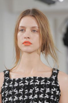 Oscar de la Renta Fall 2013 - messy, wept back bun, nude eye makeup, orange lips